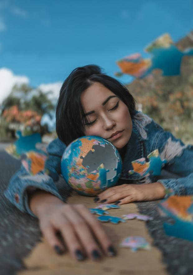 девушка положила лицо на стеклянный шар в виде глобуса