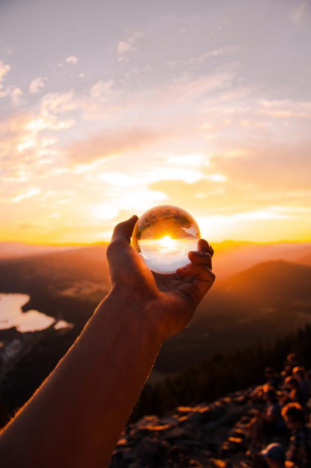 стеклянный шар лежит на протянутой к солнцу ладони