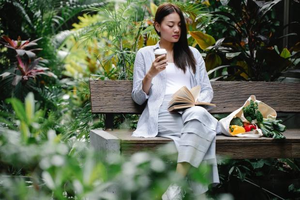 девушка читает книгу в парке на скамейке