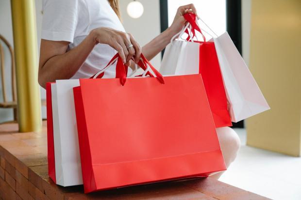 девушка в белой блузке держит пакеты для покупок красные и белые