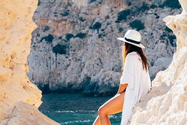 девушка в белом сидит на камнях у моря