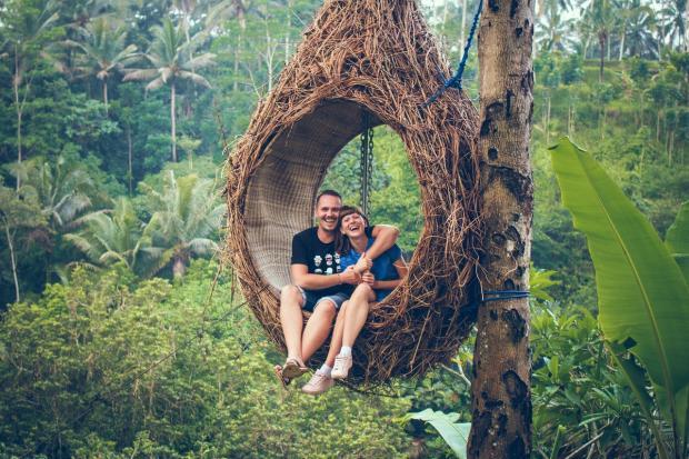 влюбленные сидят в гамаке в тропическом лесу