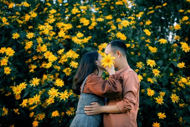 влюбленные стоят среди желтых цветов