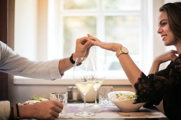 мужчина надевает кольцо на женский палец