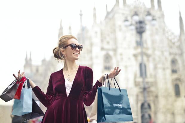 девушка стоит с покупками в пакетах