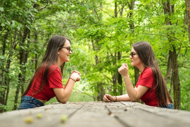 две девушки в красных футболках сидят в лесу
