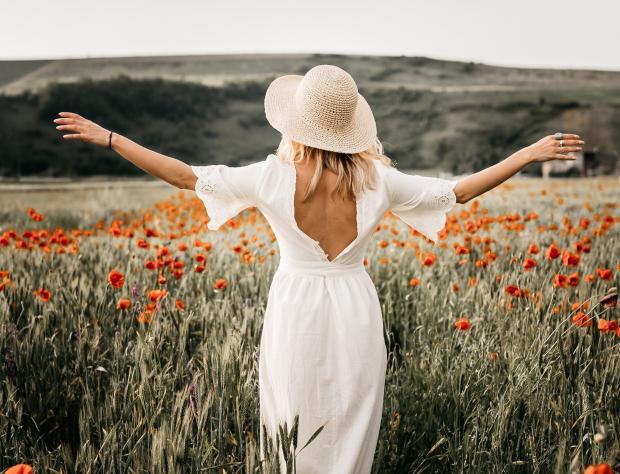 молодая девушка в белом платье и соломенной шляпе идет по полю с маками