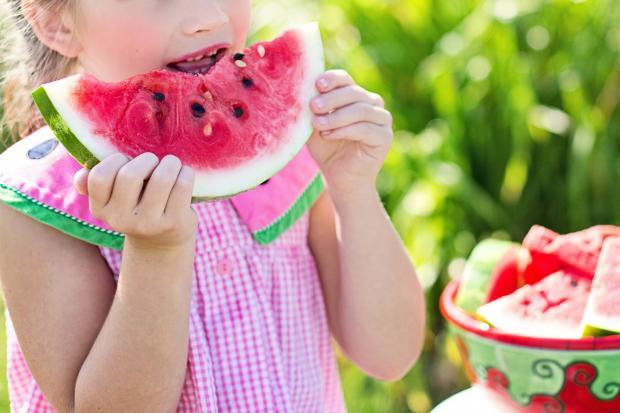 девочка в розовом платье ест арбуз