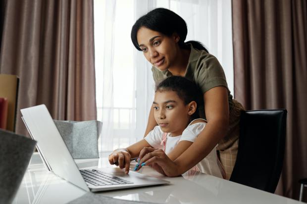 мама помогает дочке работать за ноутбуком