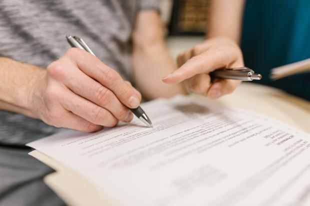 женская рука с ручкой ставит подпись на документе