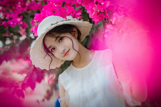 девушка в белом платье и шляпке в ветвях цветущей  сакуры