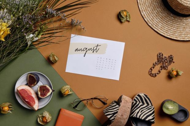 соломенная шляпка лежит на столе рядом с табличной август