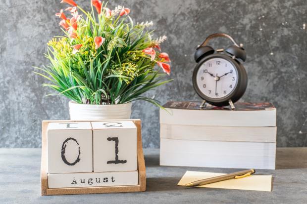 перкидной календарь с датой 1 августа стоит рядом с букетом цветов и будильником