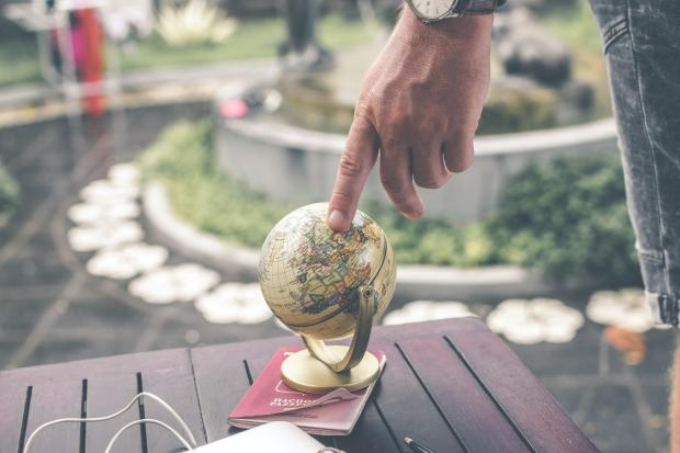 мужчина держит указательным пальцем игрушечный глобус