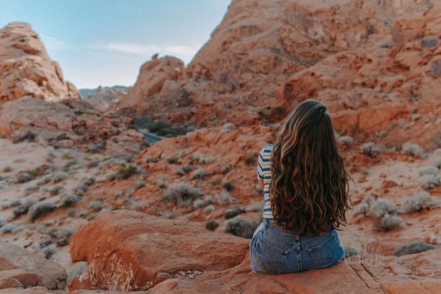 девушка сидит в горах и смотрит вдаль
