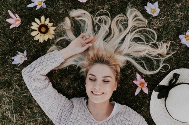 белокурая девушка с улыбкой лежит на траве