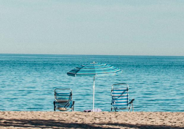 Шезлонги и зонт на берегу моря