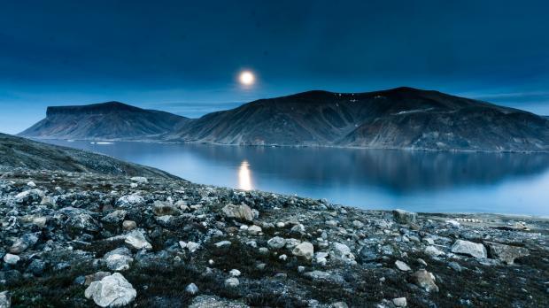 Луна стоит над морским побережьем
