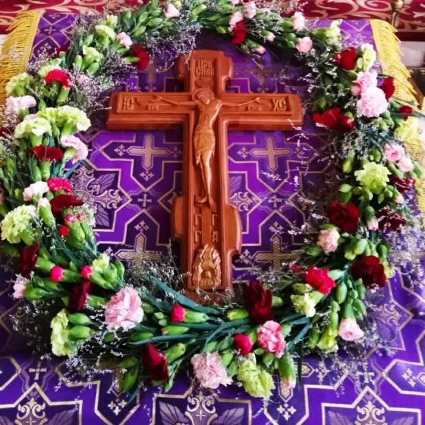 на аналое лежит крест в цветах