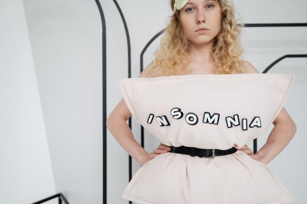 кудрявая блондинка прикрылась подушкой с надписью бессонница