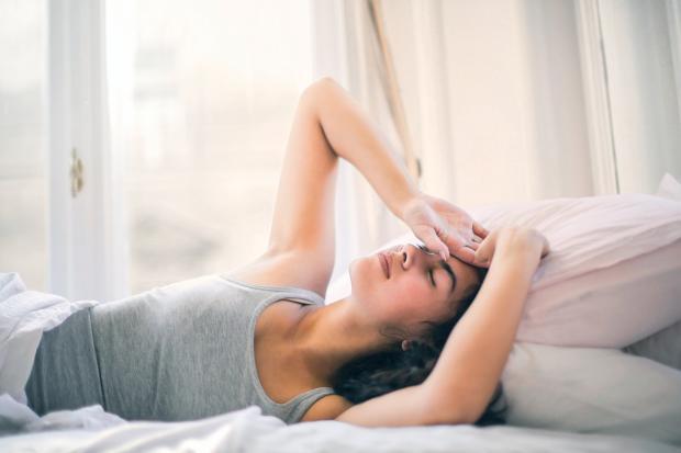 девушка в серой майке держится руками за голову лежа в кровати