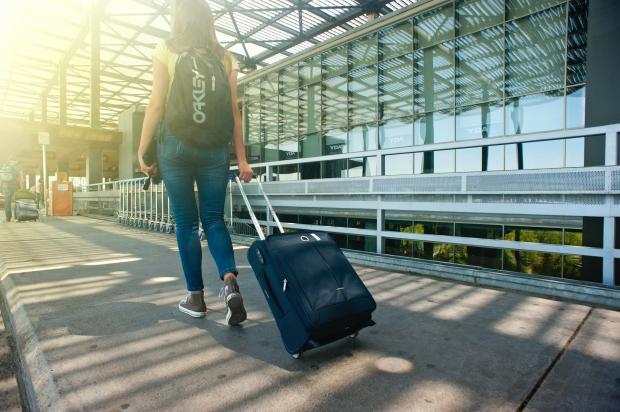 женщина с чемоданом и сумкой идет по перрону