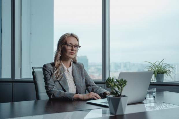 женщина в очках работает за ноутбуком в офисе