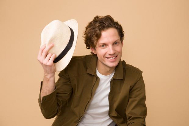 кудрявый мужчина держит в руке белую шляпу