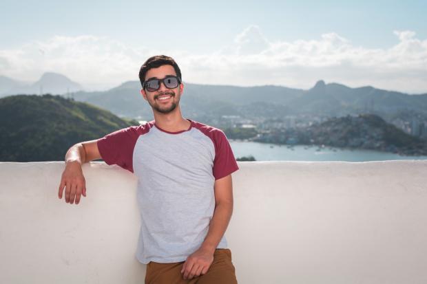 мужчина стоит на фоне гористого морского побережья