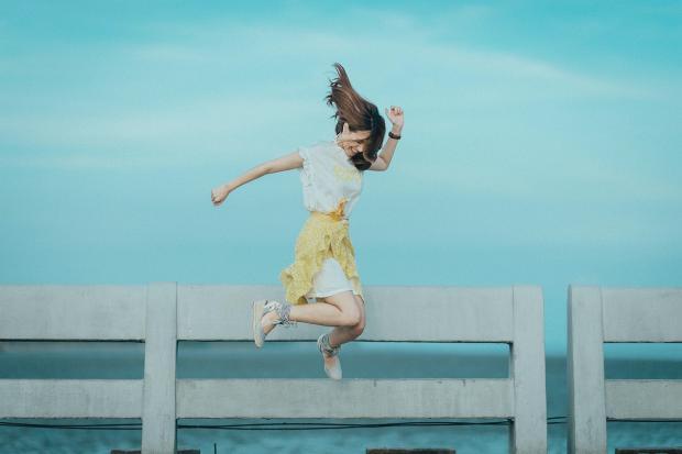 девушка в белом платье высоко прыгает