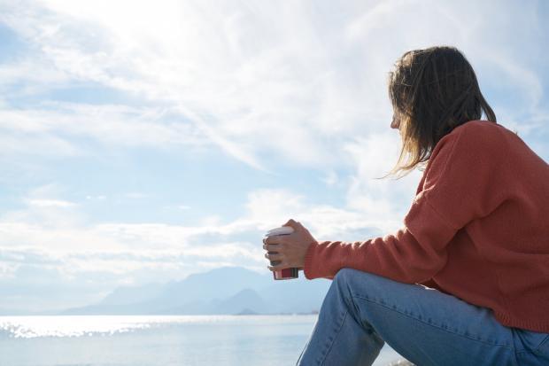 девушка в джинсах пьет кофе на берегу реки