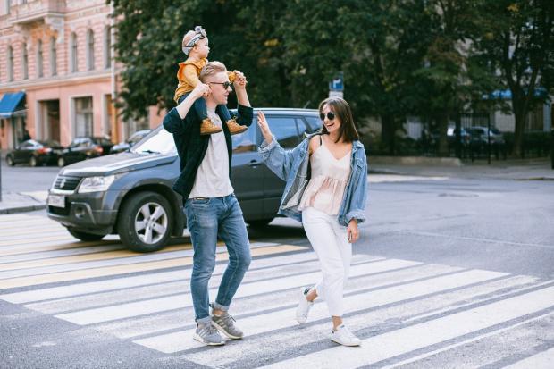 пара с ребенком идет по переходу