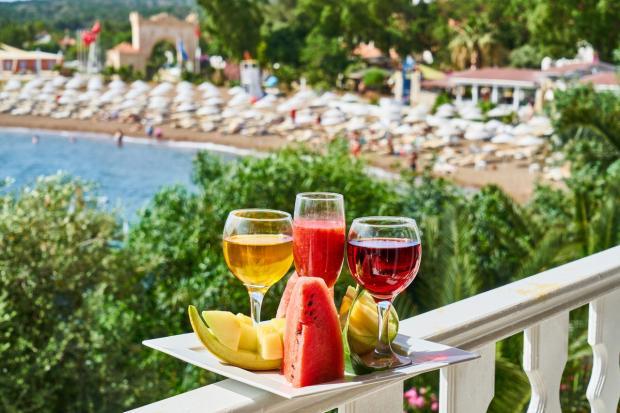 бокалы с напитками и арбузом стоят на перилах террасы над пляжем