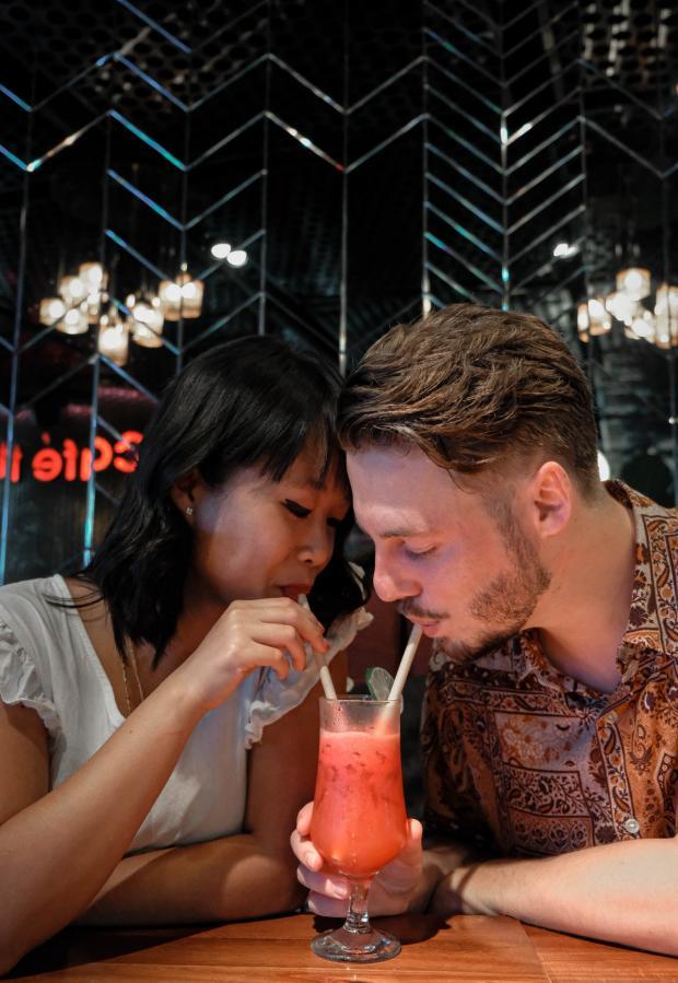 влюбленные пьют коктейль из бокала
