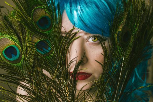 зеленоглазая девушка с синими волосами смотрит сквозь павлиньи перья