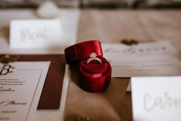 на столе в красной коробочке лежит золотое кольцо