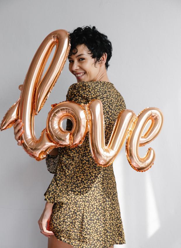 девушка держит воздушные шары с буквами любовь