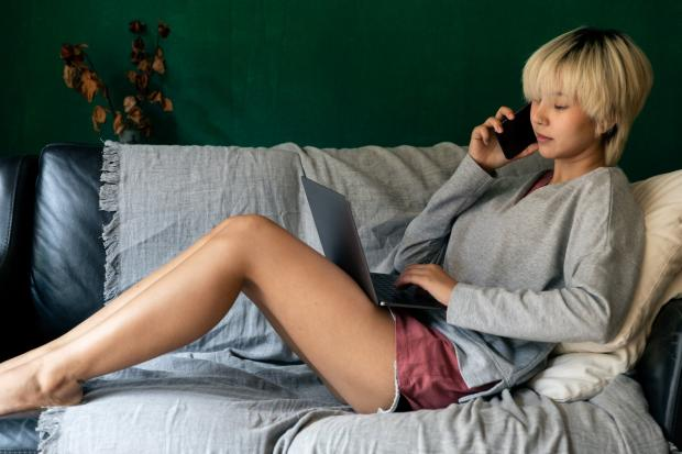 девушка разговаривает по телефону лежа на диване