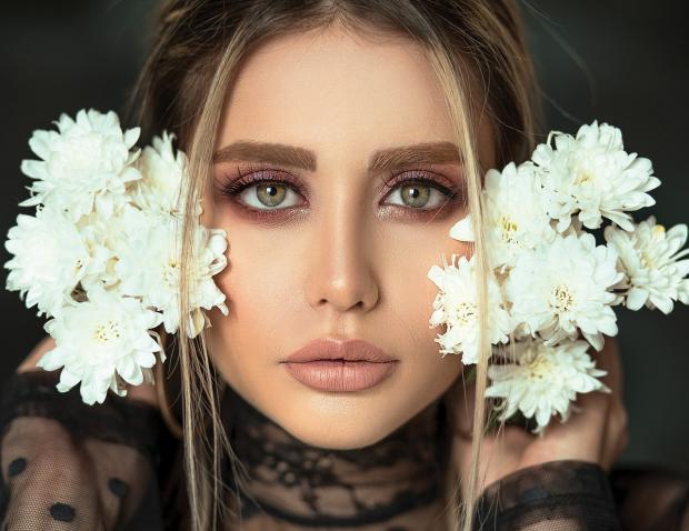 девушка держит у лица белые цветы