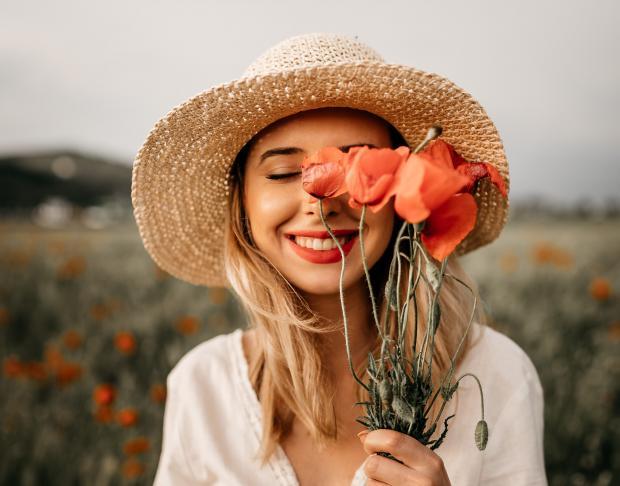 девушка в белом платье и соломенной шляпе с букетом красных полевых цветов