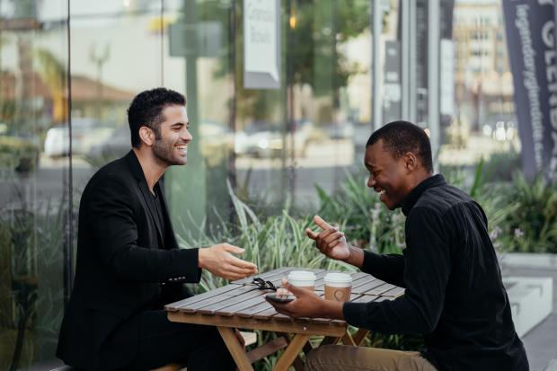 мужчины в черных костюмах сидят за столом на улице