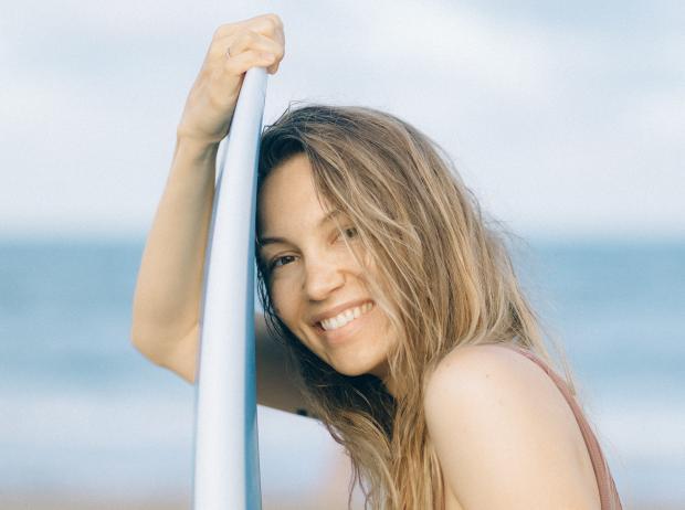 улыбающаяся девушка с доской для серфинга на пляже