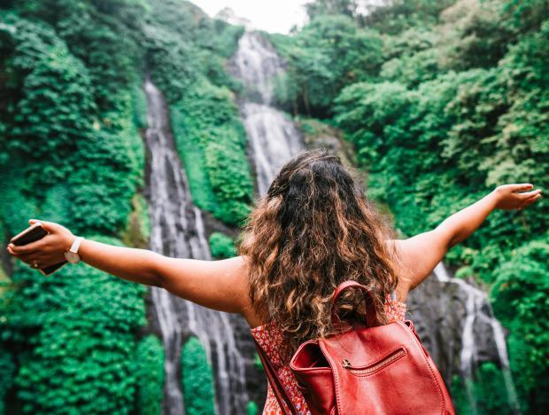 девушка с красным рюкзаком стоит возле водопада