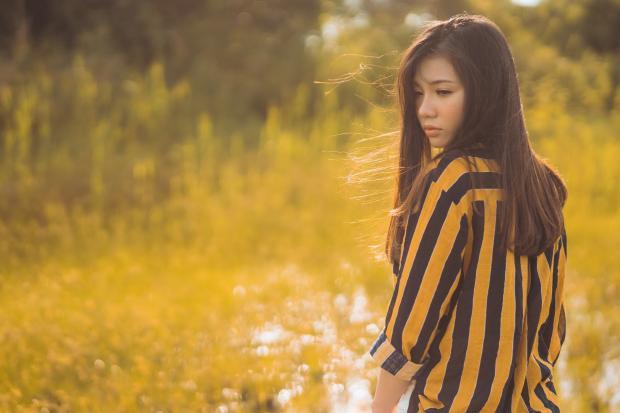 девушка в полосатой блузе стоит в поле