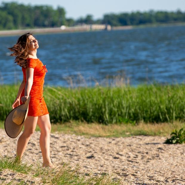девушка в красном платье идет по берегу реки
