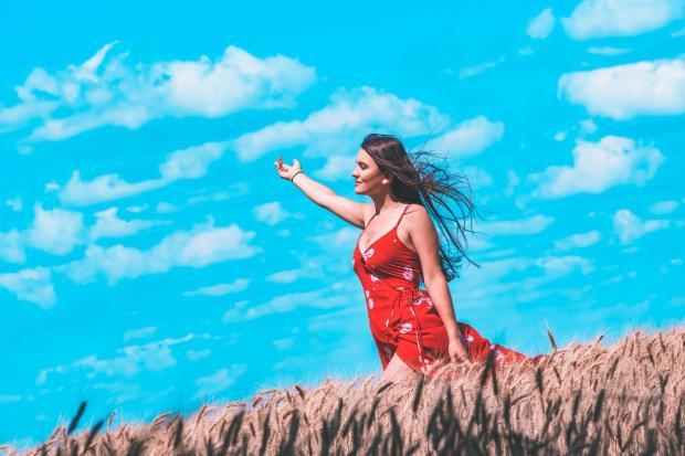 девушка в красном сарафане идет по полю