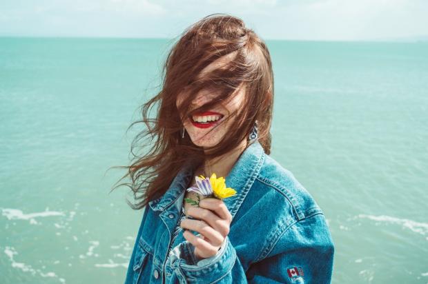 девушка в джинсовой куртке с цветами в руках смеется на фоне моря