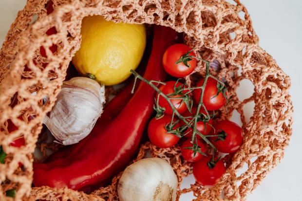 в плетеной авоське лежат овощи