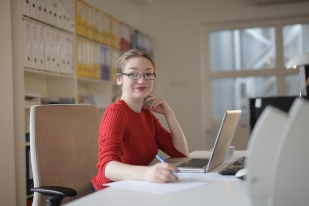 девушка в красной водолазке сидит в офисе за рабочим столом