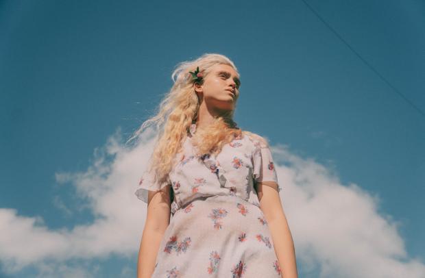 блондинка в цветастом летнем платье стоит под голубым небом